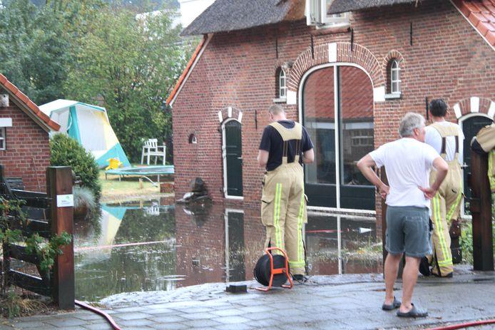 De brandweer is ter plaatse bij het ondergelopen binnenterrein aan de Keizersweg in Holten.
