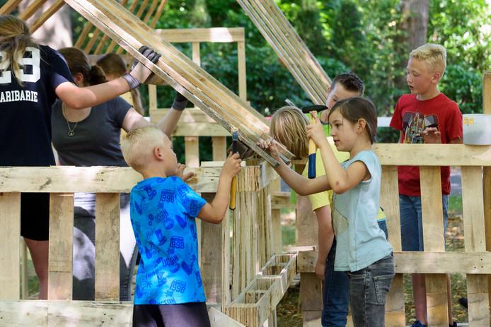 Kinderen bouwen hutten op grasveldje in Veldhoven als vakantieactiviteit