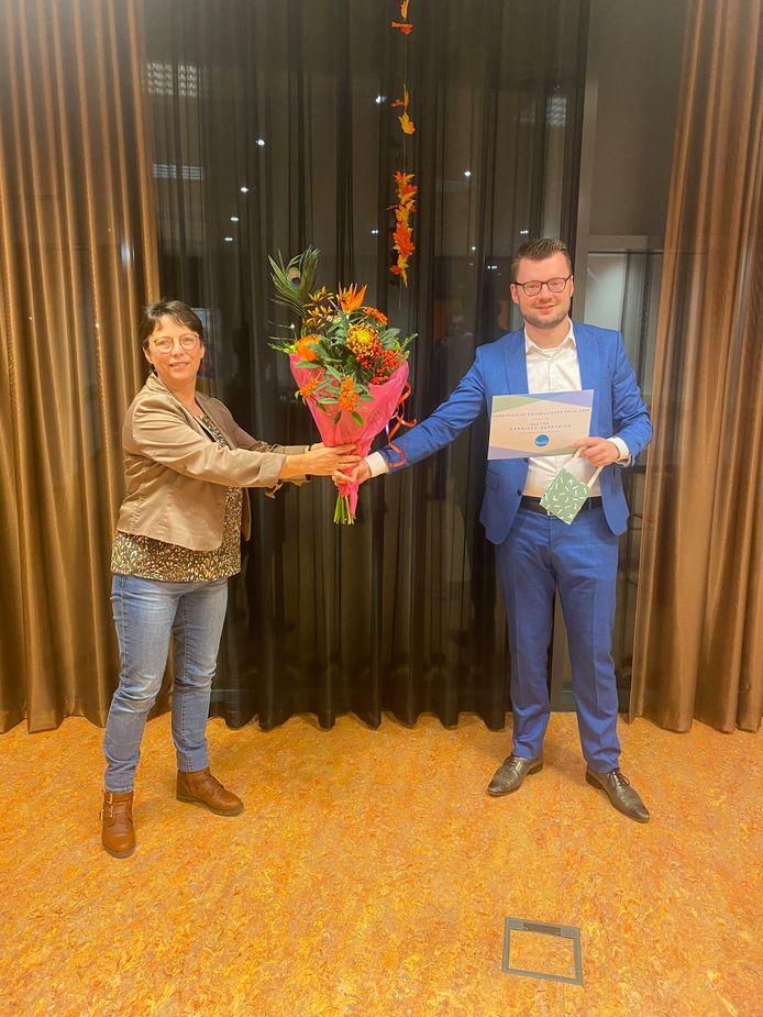 Statenlid Stijn Hesselink overhandigt bloemen en de Vrijwilligersprijs Overijssel 2020 aan Riëtte Makkinga.
