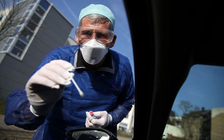 Een coronatest wordt afgenomen bij een automobilist in Halle, Duitsland.   Beeld AFP