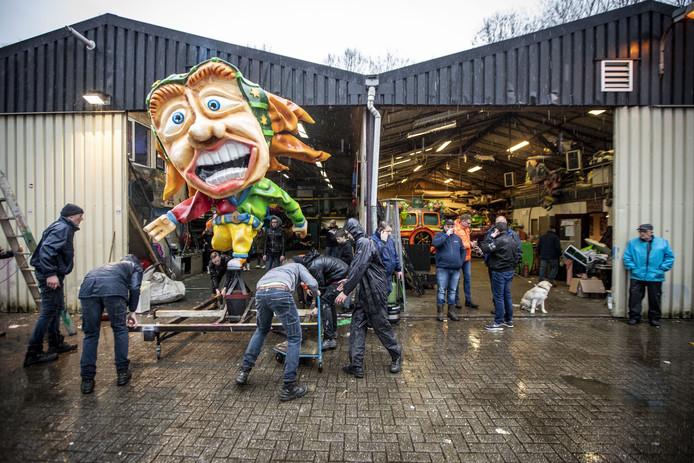 De wagenbouwers van de Blaanke Boeskeulkes schuiven een deel van hun praalwagen weer de loods in.