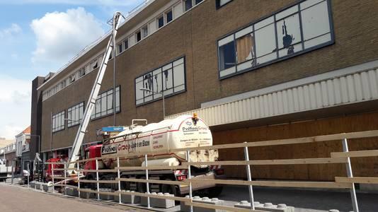 Een gespecialiseerd bedrijf verwijdert met een soort enorme stofzuiger het grind op het dak van de voormalige V&D in Bergen op Zoom.