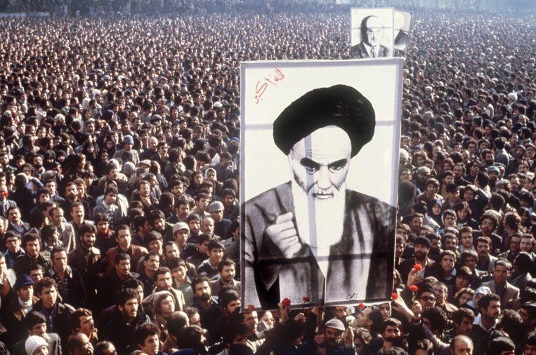 Iraniërs in Teheran dragen een poster van Ayatollah Khomeini, tijdens een demonstratie tegen de sjah, januari 1979. Beeld AFP