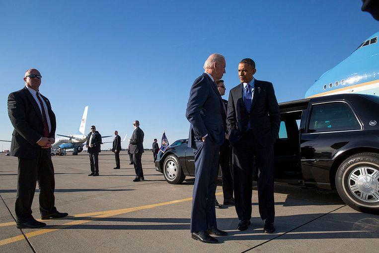 Bewaakt door Secret Servce-agenten, maken president Obama en vicepresident Biden een praatje op de luchthaven van Los Angeles. Beeld White House Photo