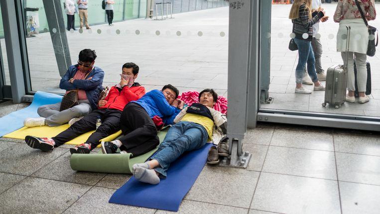 Mensen slapen op yogamatjes op Heathrow. Beeld getty