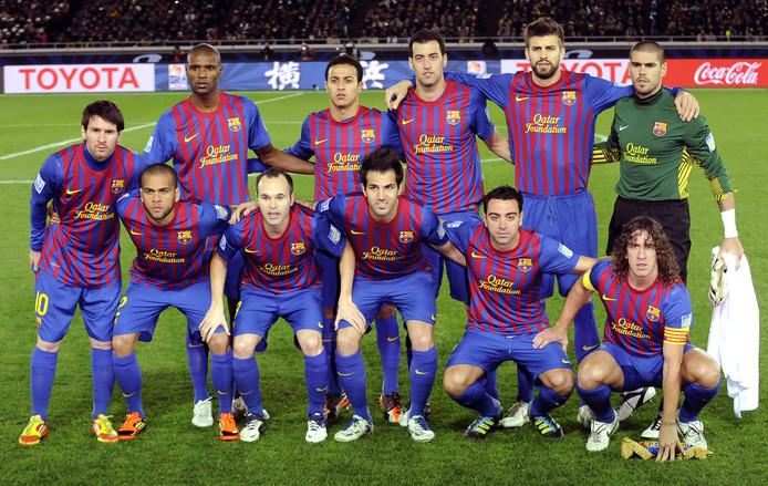 Lionel Messi op de teamfoto met Eric Abidal en Carles Puyol voor de finale van het WK voor clubs (4-0 winst op Santos) op 18 december 2011.
