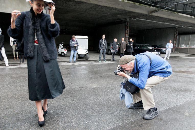 Straatfotograaf Bill Cunningham, in zijn kenmerkende blauwe werkmansjas, aan de slag bij de Paris Fashion Week in 2010. Beeld