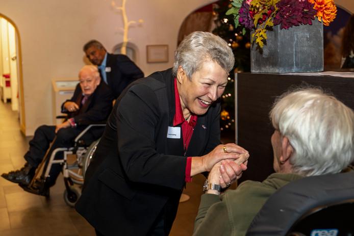 Corrie Huiding, de eerste seniorenburgemeester van Utrecht, wordt gefeliciteerd door een bewoner van het Bartholomeus Gasthuis.