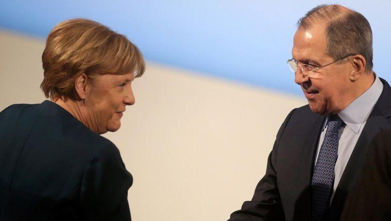 Russische minister van Buitenlandse Zaken Sergej Lavrov schudt Duitse Bondskanselier Angela Merkel de hand in München. Beeld getty