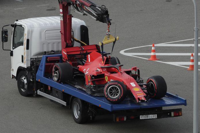 De auto van Sebastian Vettel wordt weggesleept na de crash.