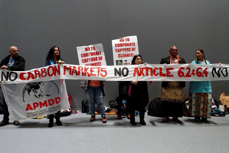 Activisten in Madrid protesteren tegen het verhandelbaar maken van klimaatcertificaten.  Beeld EPA