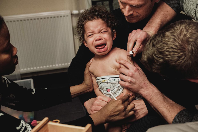 Dit kindje krijgt een vaccin toegediend in Leuven.