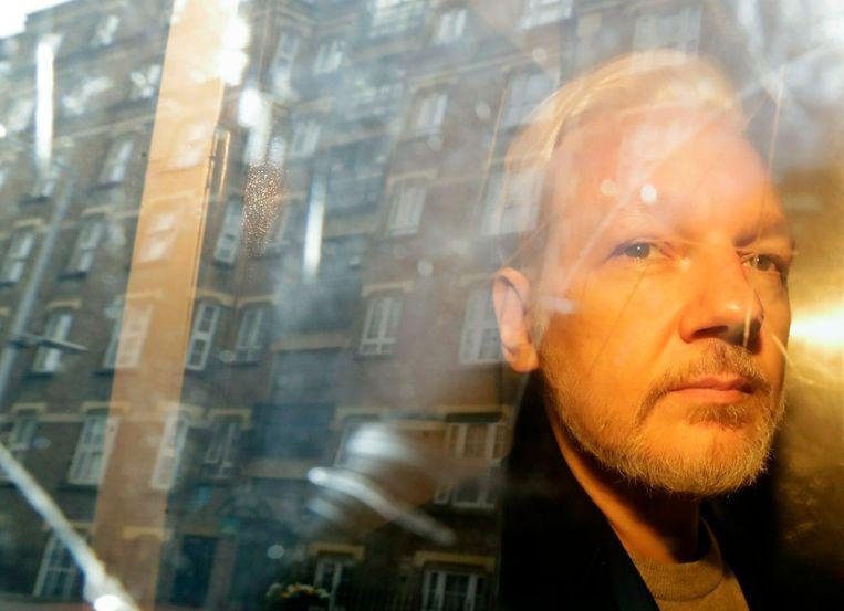 Julian Assange wordt weggevoerd van de rechtbank in Londen.  Beeld AP