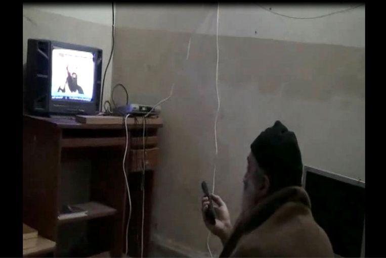 Osama bin Laden kijkt in zijn huis naar een video van zichzelf. Zelfs toen de CIA in de gaten kreeg dat hij zich verborgen hield in het complex, hadden ze nog maanden nodig om er zeker van te zijn dat het om de Al Qaida-leider ging. Beeld AFP