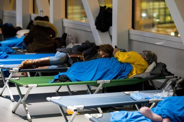 Gestrande reizigers slapen op stretchers op Schiphol. Beeld anp
