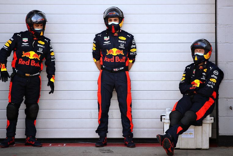 Leden van het Red Bullteam houden zich aan de voorzorgsmaatregelen in de pitstraat. Beeld Getty Images