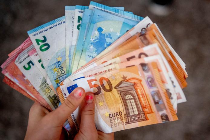ROTTERDAM - Een portomonee met geld eurobiljetten erin, met twee handen iemand gaat wat kopen. .sparen , spaargeld zwart geld rijk economie rijkdom thuis , bewaren