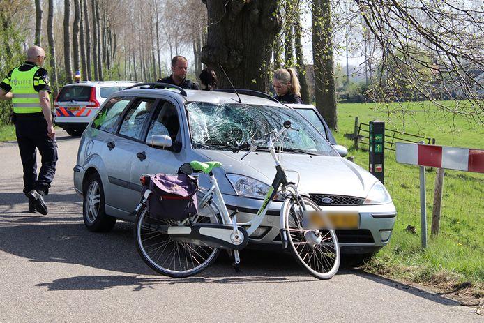 De fiets van de vrouw en de ingedeukte voorruit.