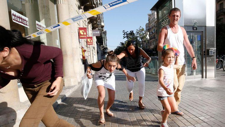 Mensen verlaten een afgezet gebied in de buurt van de Ramblas in Barcelona op donderdagmiddag. Beeld AFP