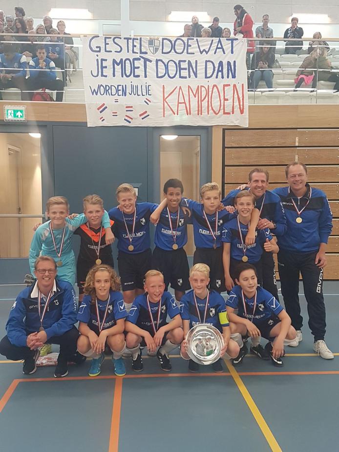 De kersverse landskampioenen zaalvoetbal (onder 13) van ZVS / Rijschool Gestel tonen de schaal aan het publiek.