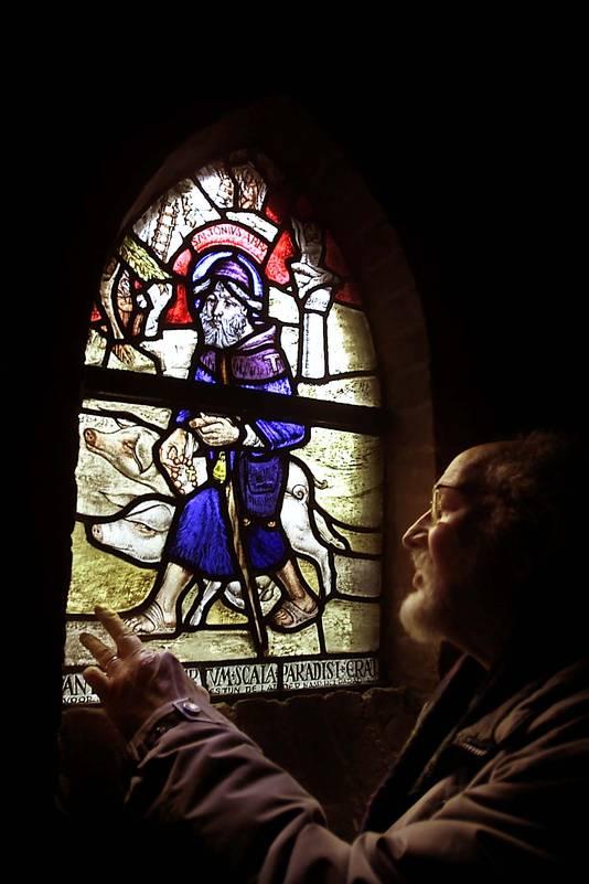 Glazenier Jan Schoenaker bij het door hem gemaakte raam van Antonius in de Oldenzaalse Plechelmusbasiliek.