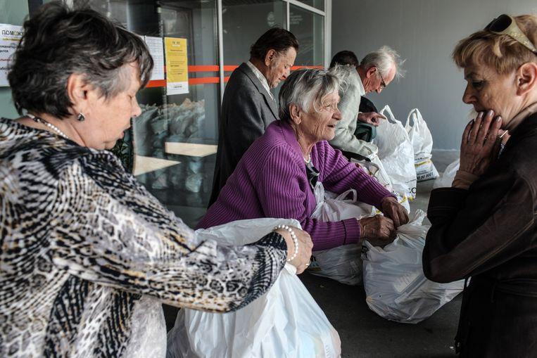 In het verlaten voetbalstadion in Donetsk delen vrijwilligers elke dag voedselpakketten uit. De noodhulp wordt betaald door Rinat Achmetov, een oligarch met een reeks fabrieken in Oost-Oekraïne. Beeld Oleksandr Tetsjynski