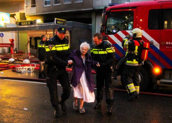 Een oudere bewoonster wordt in veiligheid gebracht nadat het Nijmeegse complex waarin ze woont, door brand is getroffen.