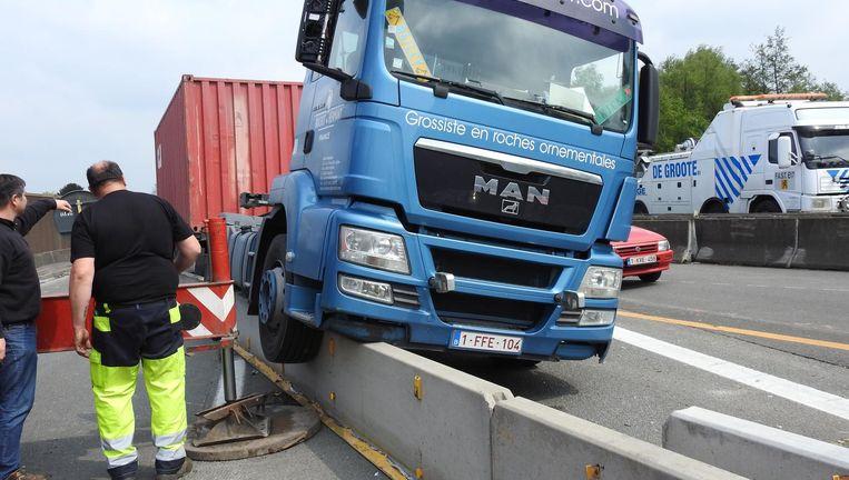 De vrachtwagen belandde op de betonblokken. Om te kunnen takelen, moest een hoogtewerker de truck omhoogtillen.