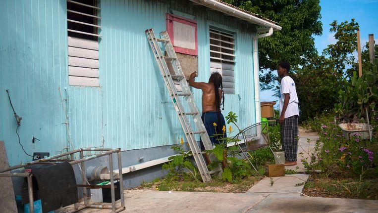 Inwoners van Marigot plaatsen houten schotten op hun ramen. Beeld afp