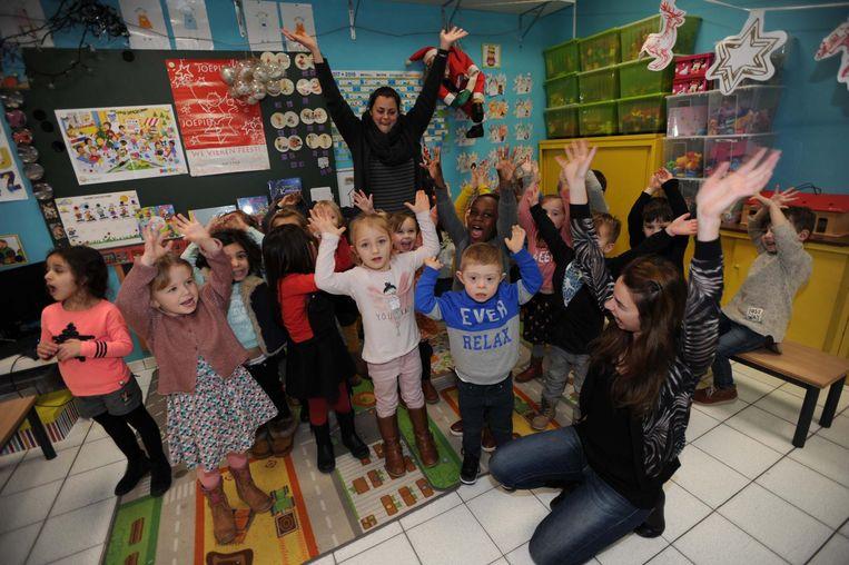 Mama Melanie (vooraan) en Juf Leen (achteraan) bouwen een feestje in de klas met Kyllyan (blauw-grijze trui) en zijn vriendjes.