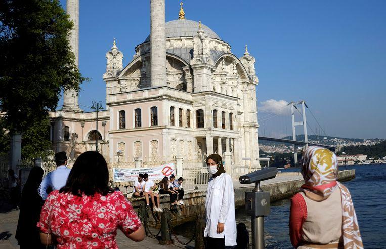 Een vrouw met een mondkapje nabij de Ortakoy Moskee in Istanbul. Reizigers uit Turkije zijn nog niet welkom in de EU. Beeld REUTERS