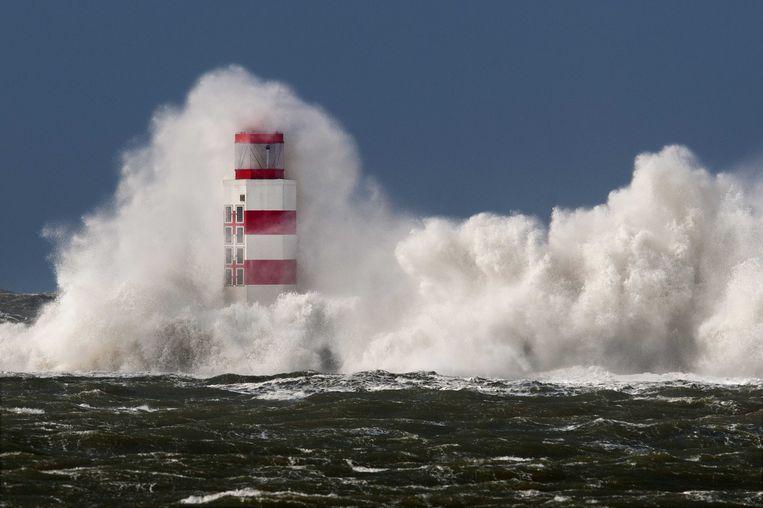 Hoge golven slaan tegen de vuurtoren aan het eind van de Noordpier bij IJmuiden. Beeld ANP