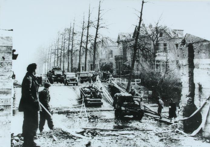 Canadese voertuigen passeren de nagenoeg drooggelegde gracht bij de Deventerweg in Zutphen, waar de Duitsers de brug hadden opgeblazen.