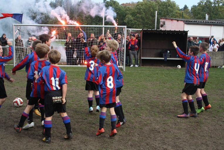 De spelertjes moedigen hun enthousiaste supporters, met bengaals vuur, aan.