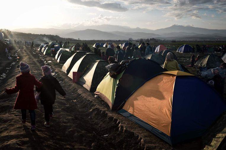 Vluchtelingen in het geïmproviseerde tentenkamp bij de Grieks-Macedonische grens. Beeld afp