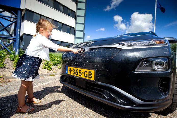 Dochtertje Isabelle op zoek naar de laadopening van de Hyundai Kona Electric