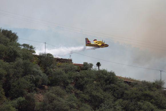 Een blusvliegtuig dropt water op Gran Canaria.
