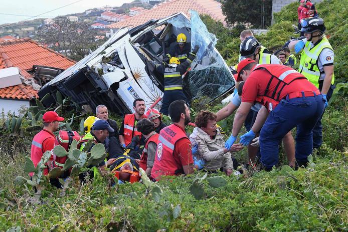 Brandweermannen helpen gewonden uit de bus.