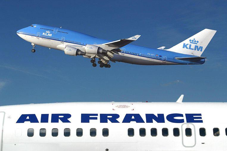 Schiphol. Een KLM Boeing 747-400 vliegt boven een Air-France vliegtuig. Beeld AFP