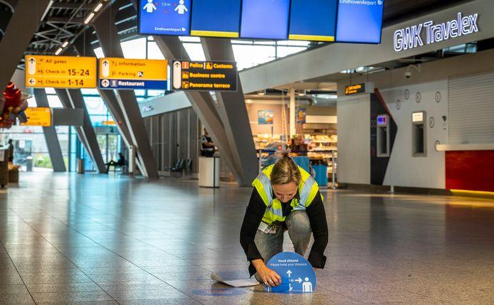 Vanaf maandag gelden er nieuwe maatregelen op Eindhoven Airport. Frederique Bot-Portheine plaatst stickers op de grond in de terminal.