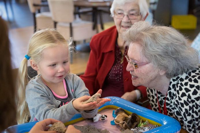 Oudereren vermaken zich met kinderen in Nieuwehagen zoals dat ook gebeurt in woonzorgcentrum De Hooghe Clock.