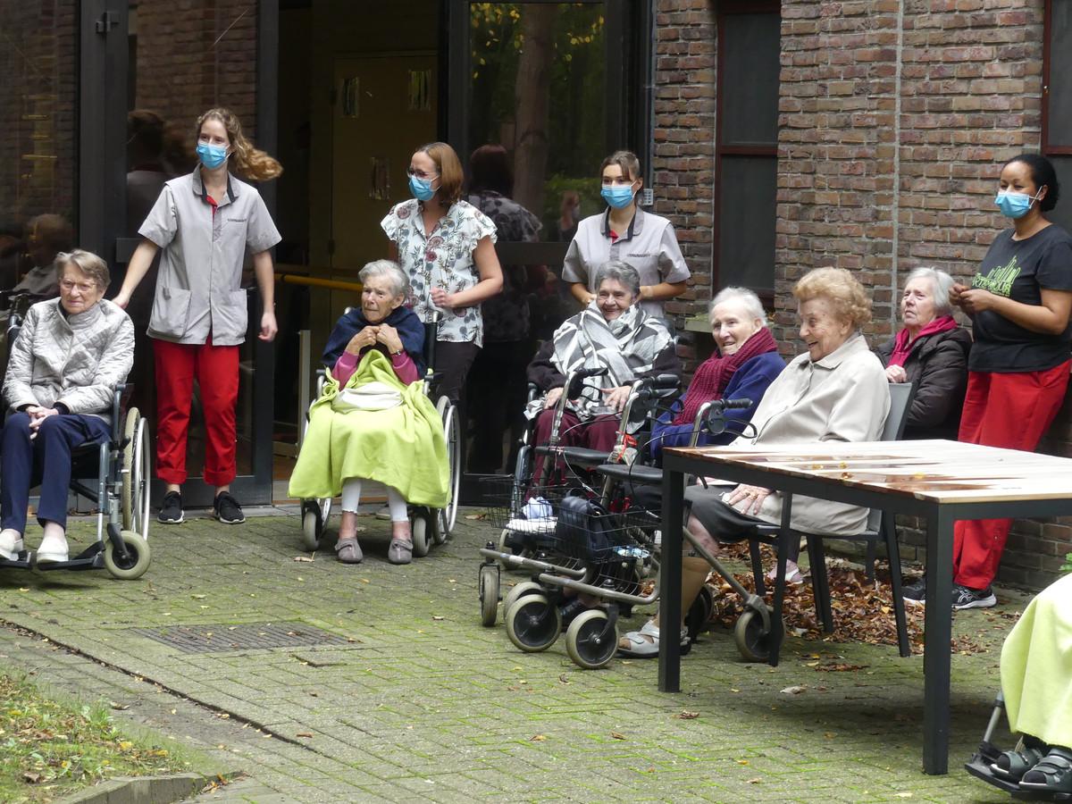 De bewoners en het personeel genieten van het optreden van de kleuters.