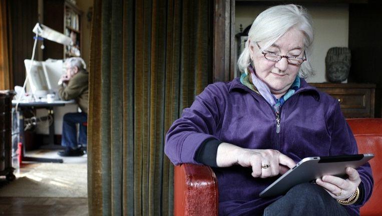 Esabeth Swane leest de krant op de iPad. Haar man heeft liever de papieren versie. Foto: Jörgen Caris Beeld