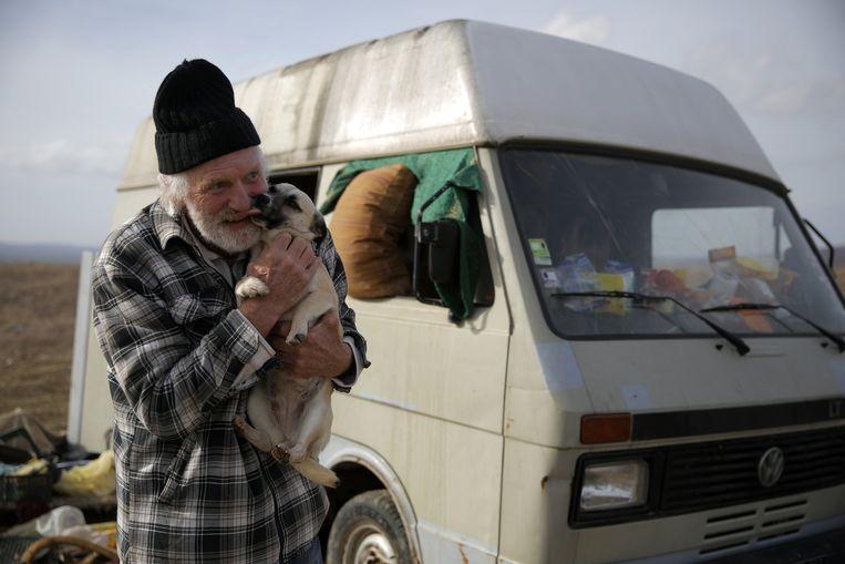 Oud-bokser Rudi Lubbers met een van zijn honden voor zijn busje bij Kosharitsa in Bulgarije. Beeld REUTERS