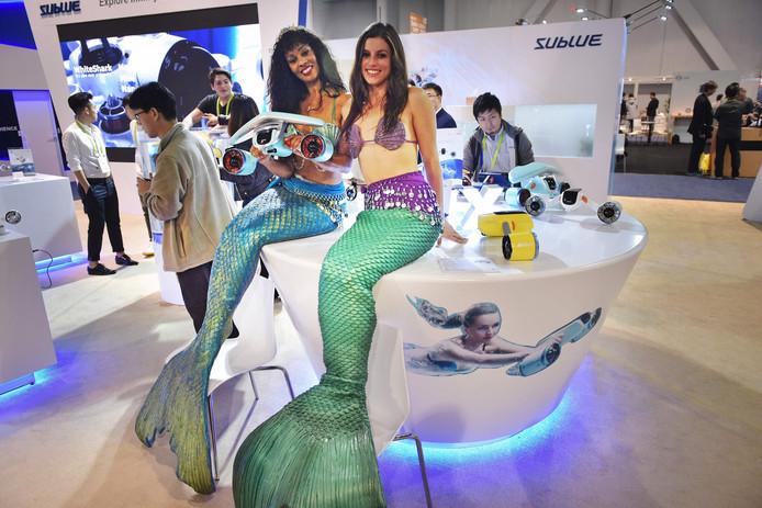 Modellen verkleed als zeemeermin promoten een onderwaterscooter tijdens de CES technologiebeurs in Las Vegas. Foto Mandel Ngan