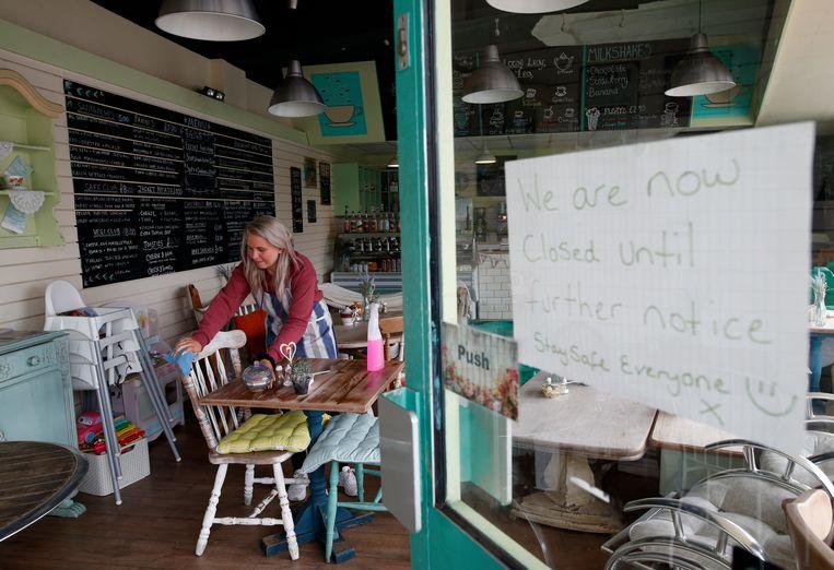 Café-eigenaar Abbie Wilson ontsmet haar stoelen tijdens de lokale lockdown in Leicester. Beeld Getty Images