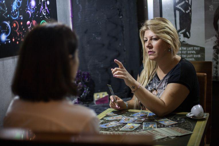 Koffiedikkijker en tarotkaartlezer Özlem Kapucuoglu ontvangt een klant aan haar tafel achter haar restaurant in Izmir. FOTO Aslihan Güclü Beeld OZLM