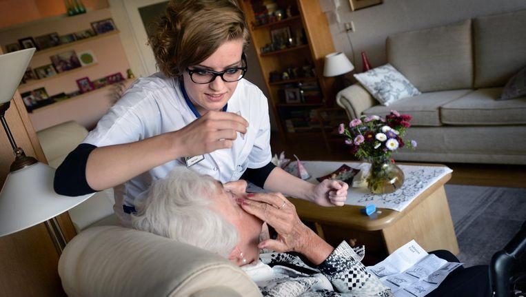 Een thuiszorgmedewerker leert een oudere vrouw hoe ze haar ogen zelf druppelt. Beeld Marcel van den Bergh / de Volkskrant