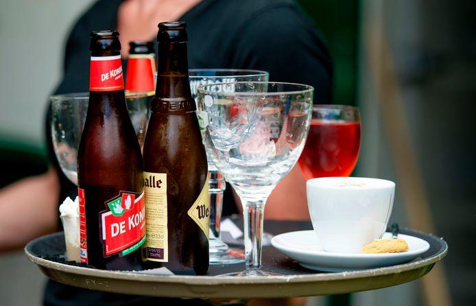 Een medewerker van een terras brengt drinken op een dienblad naar klanten.