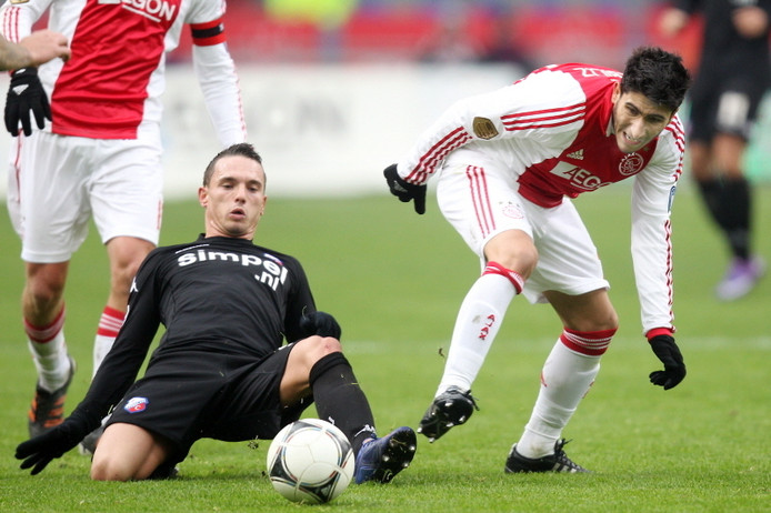 Rodney Sneijder glijdt naar de bal in de Arena. Rechts Aras Özbiliz. © PRO SHOTS